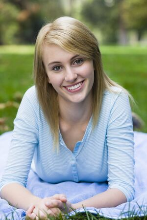 Smiling Teen Girl Lying on Blanket in Park Stock Photo