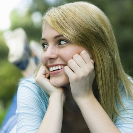 looking away from camera: Smiling Teen Girl Resting head on Her Hands Looking Away From Camera