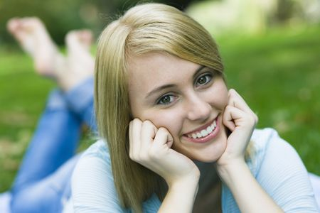 Pretty Teenage Girl Lying on Blanket in a Park Stock fotó