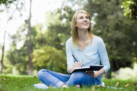 Pretty Teenage Girl Writing in Journal in Park Stock Photo