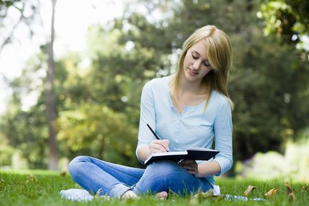 journals: Teen Girl Sitting in Park Writing in Journal Stock Photo