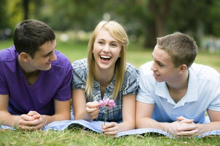 Three Smiling Teens Lying on a Blanket in a Park photo