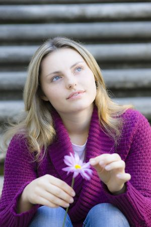 Pretty Blond Teen Girl Sitting on Stairs Holding a Daisy photo