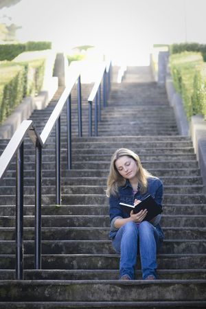 Pretty Blonde Teen Girl Sitting on a Stairway Writing in Journal photo