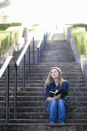 Pretty Blonde Teen Girl Sitting at Bottom of Stairway Writing in Journal