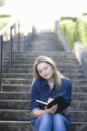 person writing: Pretty Blonde Teen Girl Sitting on a Stairway Writing in Journal Stock Photo