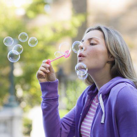 Portrait of a Pretty Blond Teen Girl Blowing Bubbles