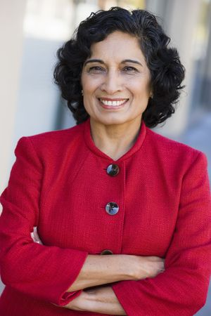 Portrait of a Smiling Indian Businesswoman Looking Directly To Camera With Arms Folded