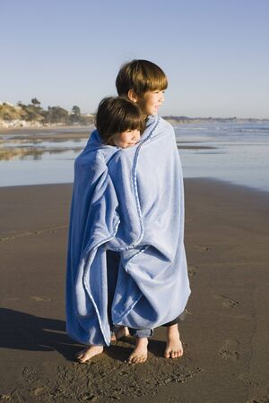 Two Little Kids Standing at Beach Wrapped in a Blanket Looking out to Sea Stock Photo