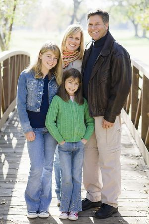 Portrait of Smiling Parents and Two Daughters Standing on a Bridge photo