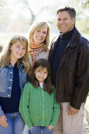 tween girl: Outdoor Portrait of a Family of Four Standing in a Park Stock Photo