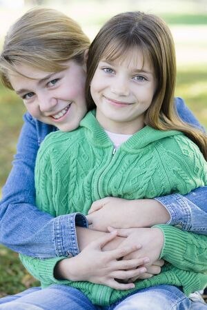 Portrait of Two Young Sisters Holding Each Other in a Park