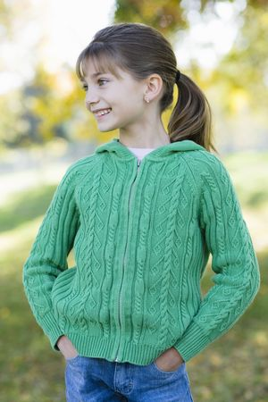 Portrait of a Cute Young Girl Standing in a Park