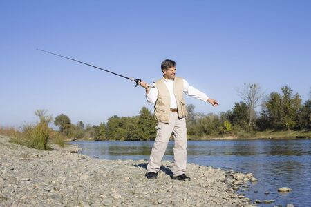 Man Standing By A River With A Fishing Pole Stock Photo