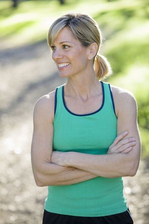 looking away from camera: Pretty Athletic Woman Standing Outdoors Looking Away From Camera