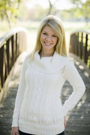 Portrait of a Pretty Blond Teen Girl Standing in a Park