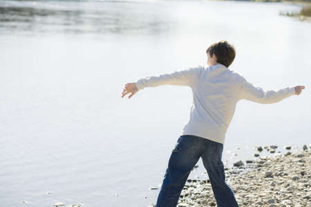 Young Boy Throwing Stones in a River 스톡 콘텐츠