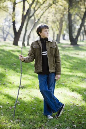 Young Boy Standing With Stick in a Park Looking Away From Camera