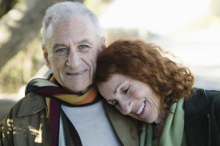 Smiling Senior Couple Standing Outside in a Park photo