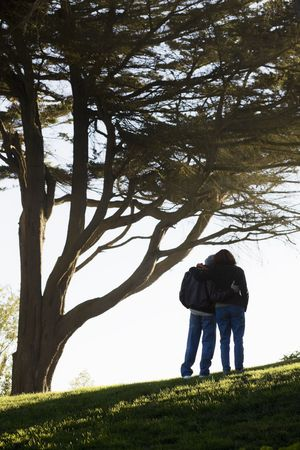 escapism: Senior Couple Holding Each Other on a Hill With Backs To Camera Stock Photo