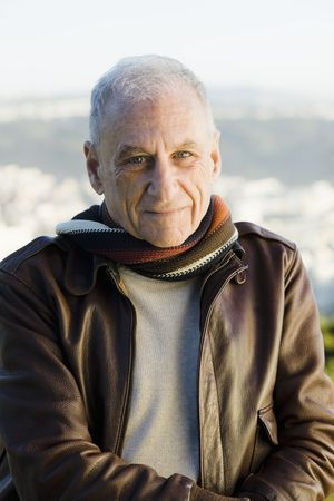 Portrait of a Senior Man in a Scarf and Leather Jacket Looking Directly To Camera photo