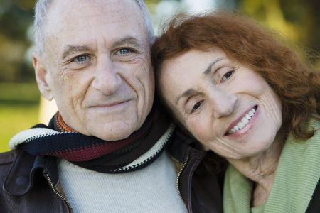 Portrait of Two Happy Seniors Leaning on Each Other Stock Photo