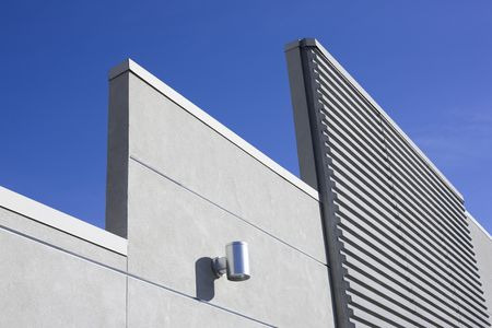 Modern Concrete Wall With Light Fixture in Front of a Bright Blue Sky