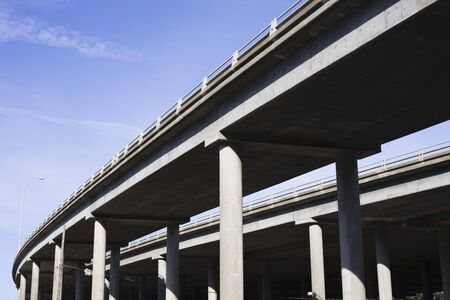 Contrasting Pillars of a Highway Overpass With a Bright Blue Sky