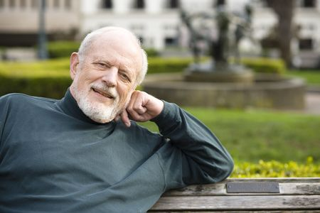 Portrait of an Elderly Gentleman Sitting on a Bench in a Park
