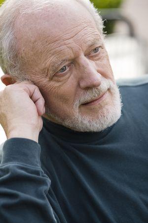 Portrait of an Elderly Gentleman Sitting on a Bench in a Park photo