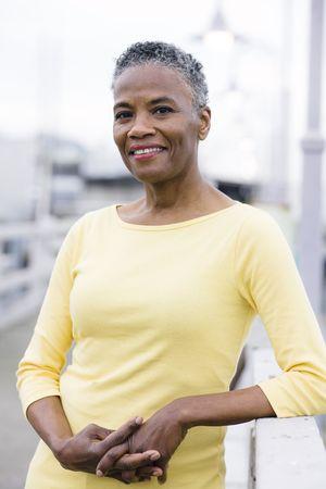 mujeres ancianas: Retrato de una hermosa mujer afroamericana permanente sobre un muelle