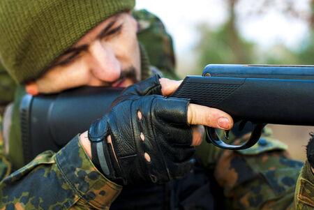 gatillo: hombre con uniforme de camuflaje aprieta el gatillo Foto de archivo