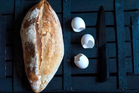 French roll, egg shells, knife on dark background photo