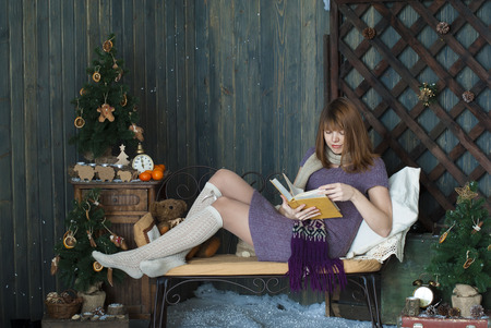 Young beautiful girl reading a book in a yellow interior Christmas