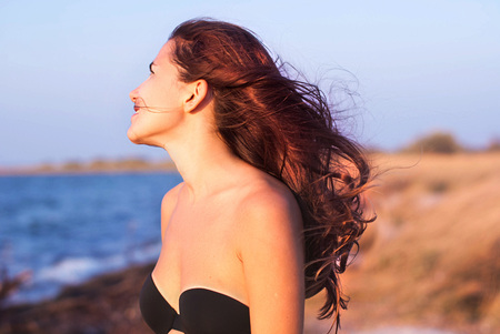 Girl with long hair in swimsuit smiles against the sea