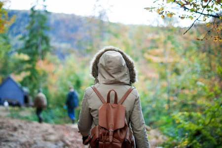 seasonality: The girl in the jacket back in the autumn forest Stock Photo