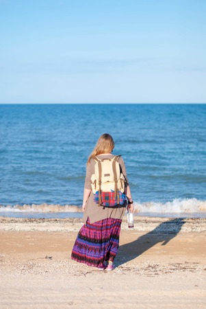 A girl stands back and looks at the sea. Hippie Girl looks at the sea. Woman with a bottle of wine is by the sea. hippie girl with an old backpack and a bottle of wine.
