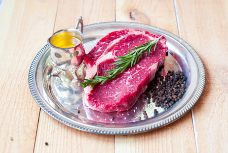 sample tray: Meat steak ribeye with olive oil and rosemary. Beef steak raw. Stock Photo