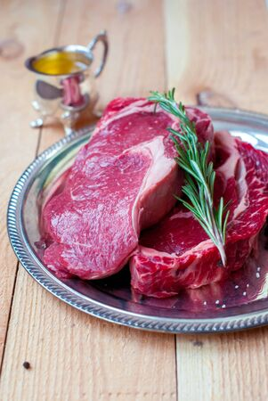 sample tray: Two ribeye steaks on a wooden table with sunflower oil and rosemary. Stock Photo