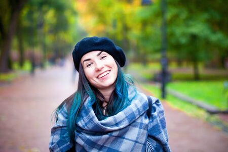 Happy beautiful girl in black beret. Woman with blue hair.