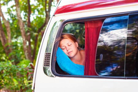 A beautiful red-haired girl is sleeping on the bus while traveling. Stock Photo