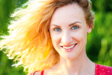 Happy middle-aged woman with blond hair smiling in backlight. The face of a beautiful girl with flying hair. Imagens