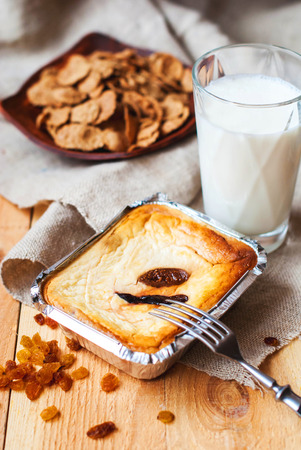 Sweet curd casserole with figs and raisins baked in the oven and milk in a glass on a wooden table. Cheesecake with figs and raisins in a baking dish for breakfast with a glass of milk. Stock Photo