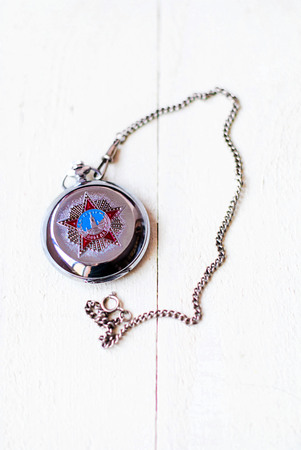 Award-winning Soviet watches for the Victory Day. Vintage pocket watch on a chain to the Victory Day with the image of the Kremlin and a star on a white wooden background.