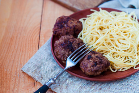 Beef cutlets with spaghetti in a rustic style. Mitbols with paste on a ceramic plate. Meat cutlets on a wooden background. Stock Photo