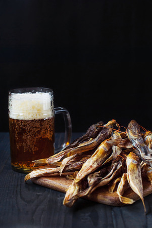 Light beer with dried fish. A glass of beer with sea gobies. Dried steers and beer. Beer and salted fish on a dark background