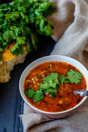 Georgian soup kharcho with cilantro and vegetables. The national Georgian dish is served with fresh lavash. Soup kharcho with vegetables and cilantro on a wooden table. Stock Photo