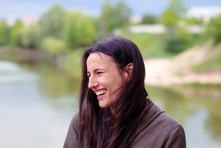A beautiful girl without makeup with long dark hair laughing near the river.