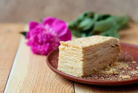 Cake Napoleon on a wooden table with a peony flower.