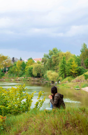 A young girl with long dark hair in a cloak with a hood sits on the river bank with her back and looks afar at nature. Stock Photo